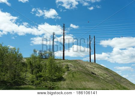 Cellular and power line poles and towers on top of a green mountain with blue sky background