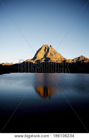 Midi Dossau Peak reflected in Ayous lake. Ossau Valley, Pyrenees National Park, Pyrenees, France.