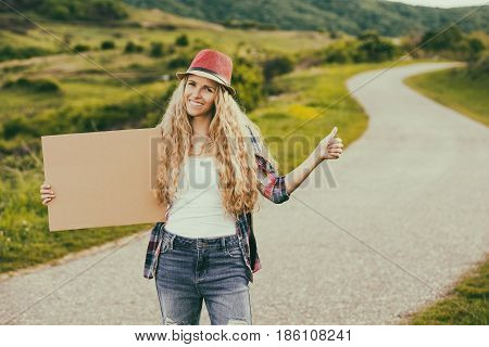 Beautiful young woman holding blank cardboard and hitchhiking at the country road.