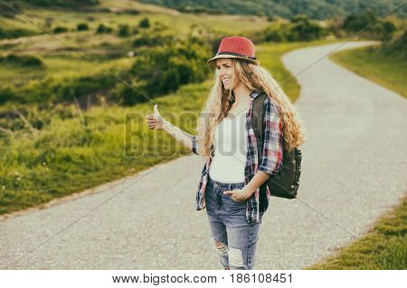 Beautiful young woman hitchhiking at the country road.