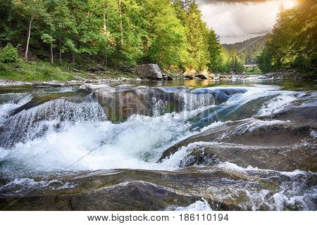 Spring river landscape. Fast stream in a mountain forest on a spring time.