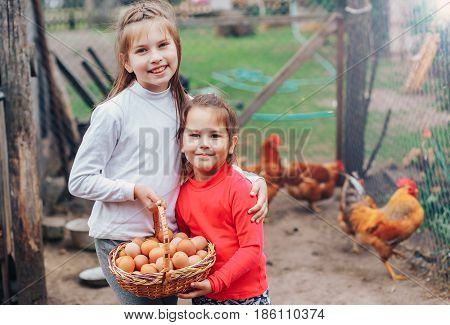 two little girls holding a basket full of fresh eggs on the farm