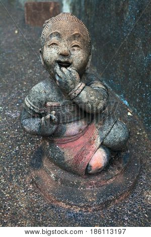 A sculpture of a laughing child. The girl covers his mouth with palm. Thailand temple complex.