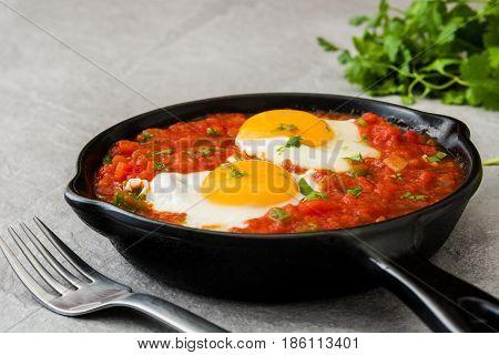 Mexican breakfast: Huevos rancheros in iron frying pan on gray stone