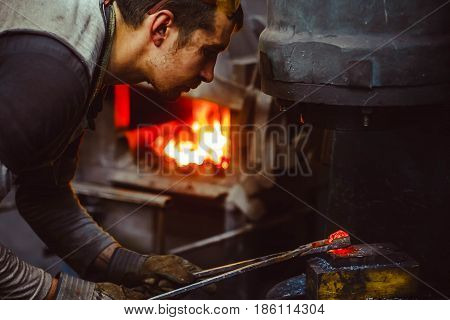 blacksmith working in the forge on auto hammer