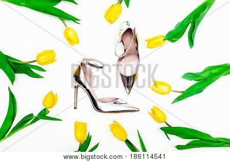 Silver high heels pump shoes. Bright floral background.