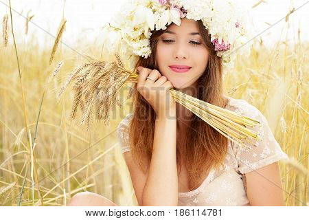 Carefree Adolescence. Portrait Of Attractive Young Woman With Flowers On Her Head Keeping Wheat In H