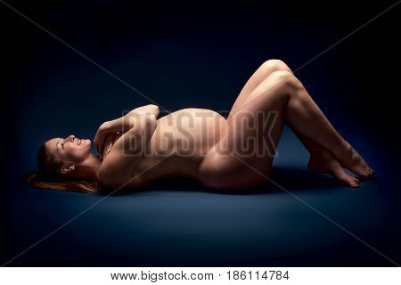 Young beauty and sexy caucasian pregnant woman on blue studio background
