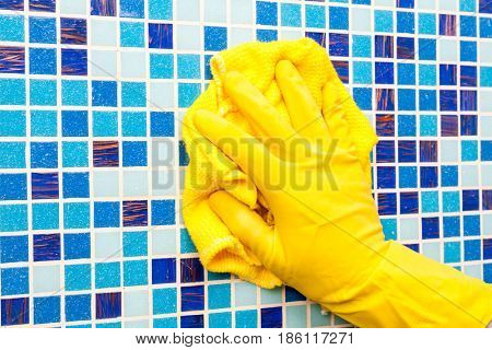 Person doing chores in bathroom at home cleaning tiled wall with microfiber towel