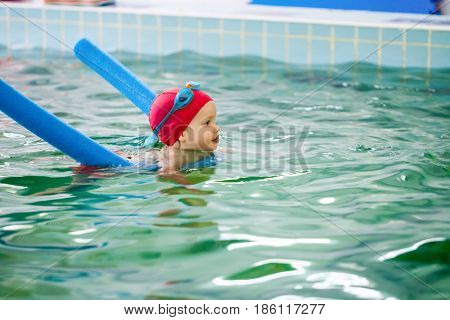 Toddler girl learning to swim with a pool noodle in a seawater swimming pool