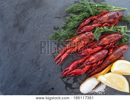 Fresh boiled crayfish on a dark slate background