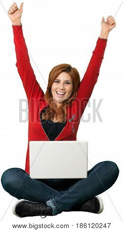 Red headed woman sitting crosslegged and celebrating with an open laptop in front of her