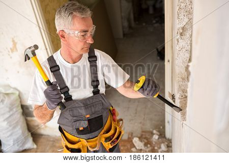 Senior Man Working With Hammer And Tool While Demolish Wall