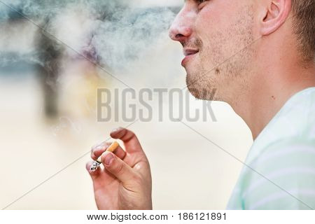 Smoking problem addiction to nicotine concept. Adult man in white shirt smoking cigarette outside.