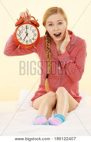 Shocked Woman Wearing Pajamas Holding Clock