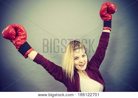 Sporty woman wearing red boxing gloves winning fight being motivated feeling relief and happiness. Studio shot on dark background.