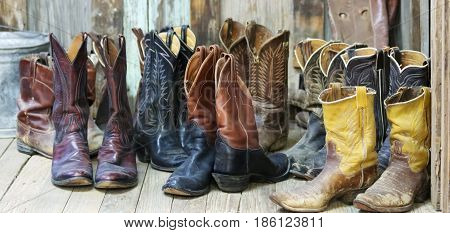 A Grouping of Ten Pairs of Old Cowboy Boots on a Plank Bunkhouse Floor