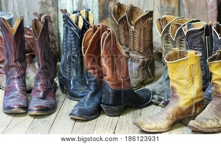 A Grouping of Nine Pairs of Old Cowboy Boots on a Plank Bunkhouse Floor