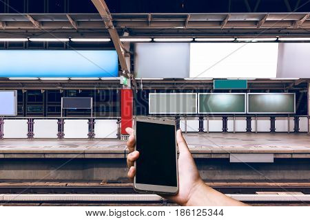 Adverting billboard background Close up hand holding cell phone with blank screen for your advertising or promotional content watching during wait at train station It's dicut save with paths file.