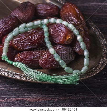 Dates Fruit And Rosary Still Life, On A Dark Wooden Background. Ramadan Food Concept.