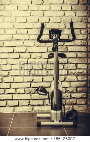 Stationary training exercise bicycle in fitness center on wall background