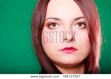 Hair care hairdresser and hair stylist. Young red haired woman with classical coiffure on green background. Studio shot.