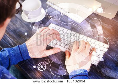 Man using keyboard with creative digital pattern placed on wooden office desktop with coffee cup and other items. Technology concept