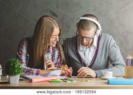 Attractive white businessman and woman working on creative project together. They are using electronic devices and listening to music through at workplace