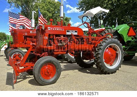 YANKTON, SOUTH DAKOTA, August 19, 2106: Restored  Farmall Cub and C tractors  bearing flags displayed at the annual Riverboat Days celebrated the third weekend of August in Yankton, South Dakota,