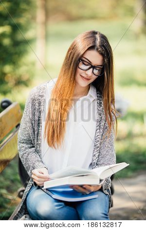 Beautiful And Happy Young Student Girl Sitting On Bench, Holding Book In Her Hands, Smiling And Look