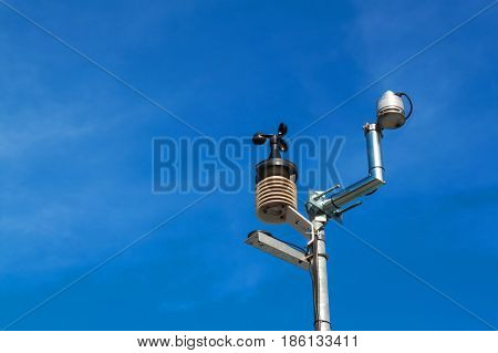 Anemometer on blue sky. Weather measuring instrument wind cup meter and direction