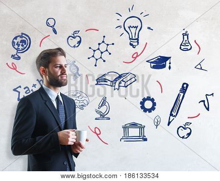 Handsome young businessman drinking coffee on concrete background with scientific drawings. Education concept
