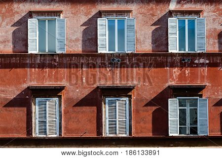 Six windows of an ancient building in Rome, Italy. Facade of an ancient building in the historic center of the Italian capital. Brown concrete wall. Some windows have shutters open, others are closed.