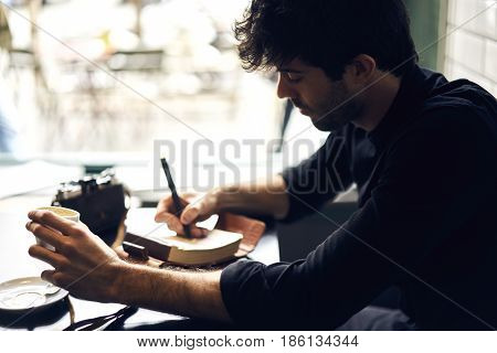 Popular detective stories brainstorming and writing new text noting ideas into personal organizer inspiring by atmosphere in cafe choosing photo for illustration