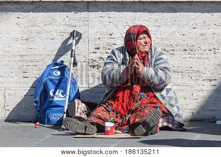 ROMA, ITALY. March 11, 2016: Homeless beggar. Woman asking for alms in street in Rome Italy. An elderly woman with her hands folded in prayer is sitting in the middle of the street to passersby.