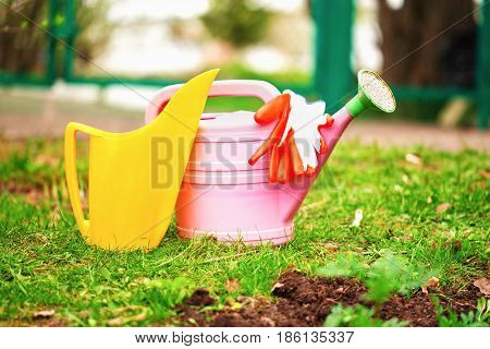 Garden watering cans and gloves on a lawn. A pink and yellow watering can stand on a green grass in a garden