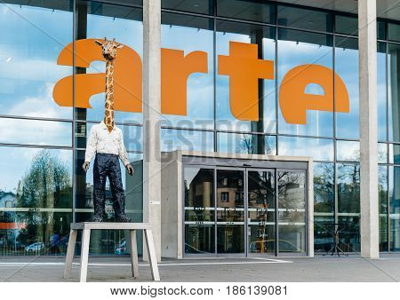 STRASBOURG FRANCE - Apr 12 2017: Arte (Association Relative a la Television Europeenne) television headquarter in Strasbourg with the L'homme-girafe Der Giraffenmann statue monument by Stephan Balkenhol.