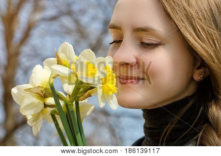 Young Women Enjoy The Bouquet Of Daffodils, Close-up
