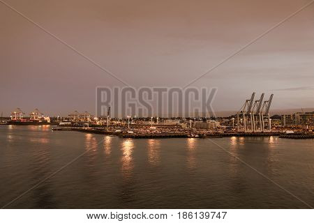 Auckland New Zealand - March 6 2017: Overview of the commercial harbor at sunset with container terminal and ships. Lights on the docks reflected in the water.
