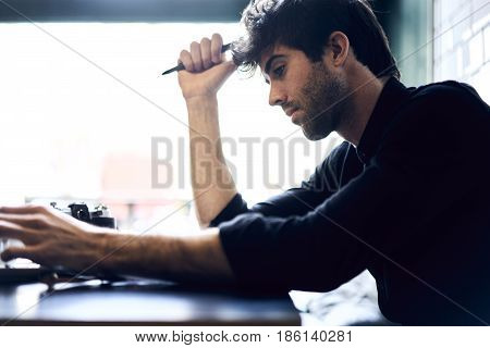 Journalist thinking over his reportage writing down best ideas into notebook creating article for publication working hard in morning sitting in office