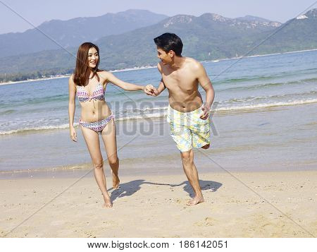 young asian couple having fun on beach.