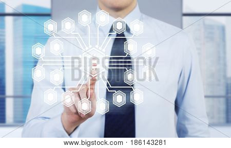 Close up of an unrecognisable businessman wearing a black tie and touching a bitcoin network hologram in his office.