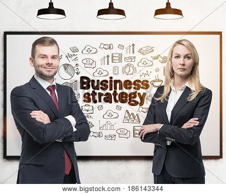 Bearded young businessman and his blond beautiful colleague are standing with crossed arms near a whiteboard with a business strategy sketch. Toned image