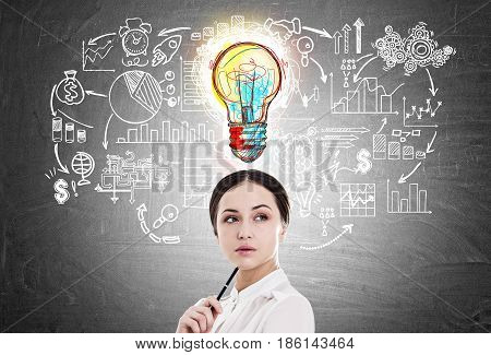 Close up of a young businesswoman holding a pen. She is standing near a blackboard with a start up sketch and a small colorful light bulb icon