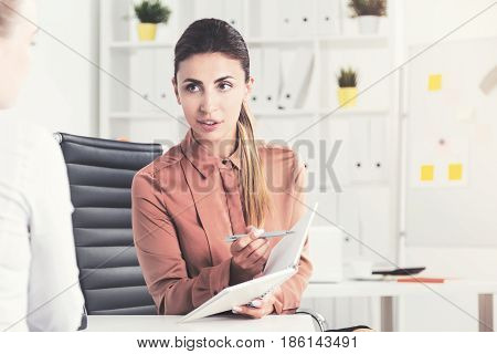 Portrait of a serious businesswoman with a ponytail showing her notes to a colleague off camera. Tone image