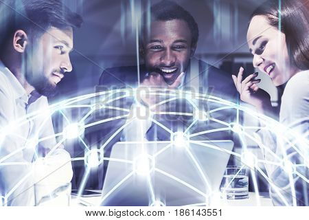 Three business partners are sitting at a table with a laptop and brainstorming trying to find the best strategy. Network hologram. Toned image