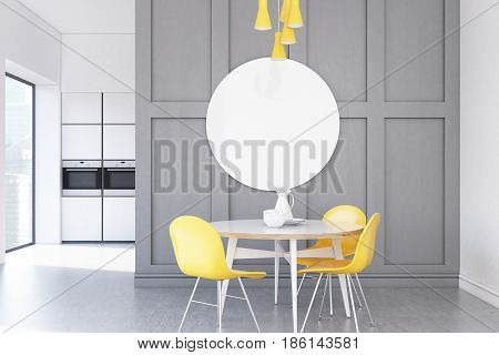 Minimalistic gray kitchen interior with a small round table surrounded by yellow chairs and a round poster above it. 3d rendering mock up