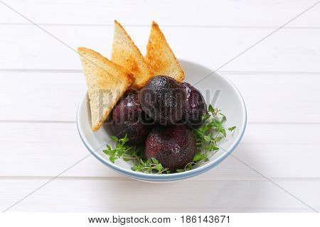 bowl of baked whole beet with toasts on white wooden background