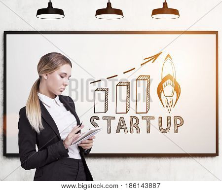 Side view of a blond businesswoman with a notebook standing near a whiteboard with a start up graph on it. Toned image