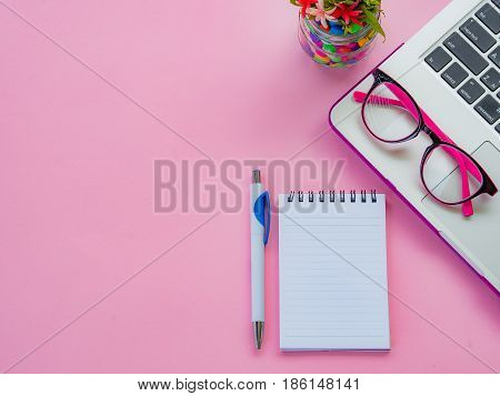Flat lay top view office table desk frame. feminine desk workspace with office accessories including laptop note book white pen coffee cup pink glassesearphone and flower on pink background.